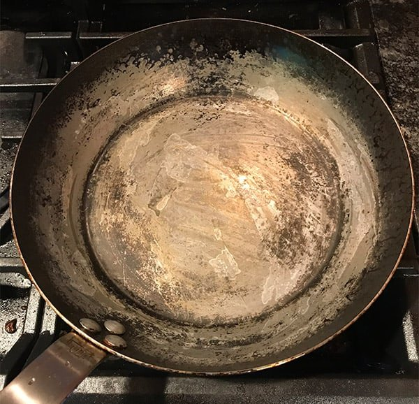 Carbon steel pan with seasoning stripped off due to acidic foods